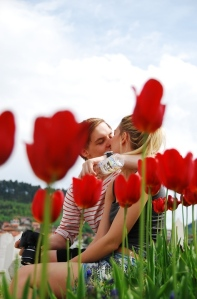 The blurry tulips in front of the actual subjects help create a depth in the photo. The red tulips also add to the feeling of love.